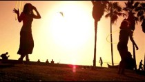 Slow motion lens flare shot of hula hoop performance by two women near Venice Beach, California