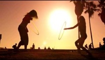 Lens flare shot of two women with hula hoops filmed in slow motion near Venice Beach, California