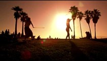 Lens flare shot of people strolling near Venice Beach, California filmed in slow motion