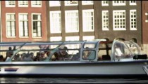 Static shot of a tour boat filled with tourists cruising in the Amsterdam waterway.