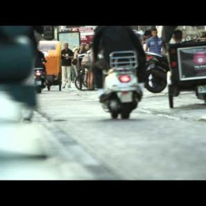 Tracking shot of people on sidewalks and people riding motorcycles down a street in Amsterdam