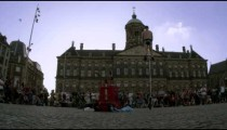 Shot of a juggler on a unicycle perfroming in front of the Royal Palace Amsterdam at Dam Square