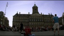Street performer preparing for his performance in front of the Royal Palace Amsterdam at Dam Square