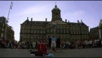 Three men assisting a street performer in front of Royal Palace Amsterdam at Dam Square
