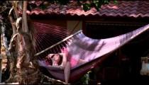 Bikini-clad woman swings in hammock at beachfront house