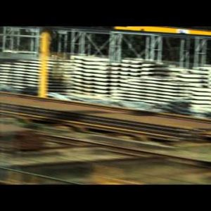 Tracking shot of buildings and pallets alongside train tracks in Amsterdam