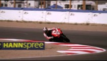 Slow motion shot of motorcycle racers turning at a curve