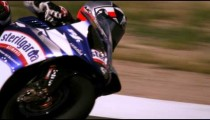 Slow motion shot of a motorcycle racer maneuvering at a curve on a race track