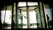 Man walk through revolving door. Vintage stylized video clip.