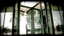 People walk through revolving door 1. Vintage stylized video clip.