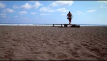Male surfer runs past camera to stand on beach driftwood
