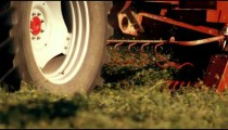 Close-up shot of the bottom of a hay baler as it gathers hay from the ground