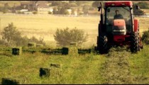 Static shot of farmer gathering hay using tractor