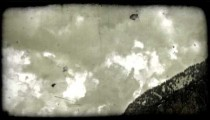 Clouds drift by mountainside. Vintage stylized video clip.