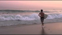 Male surfer running into the ocean, leaping onto his surfboard