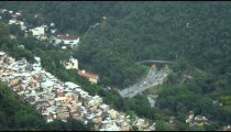 A paraglider flies over a city bluff overlooking a tunneled intersection in Rio de Janeiro