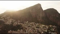 Aerial footage of city and mountain with sunlight.