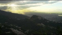 Static shot of the sun coming through the clouds over Rio de Janeiro's hills.