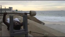 Man weightlifting at Ipanema beach in Rio de Janeiro.