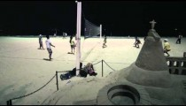 Panning shot from sandcastle to volleyball players at night.