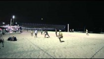 Static shot of volleyball player in yellow jersey and hat hitting volleyball and falling over.