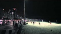 Slow panning shot of volleyball game on beach and street with traffic.