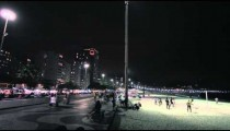 Static shot of volleyball game and street with traffic in Copacabana.