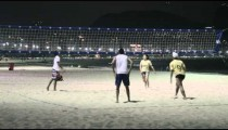 Static shot of volleyball game on beach with aggressive player in yellow shirt and white hat.
