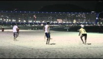 Night volleyball game on beach.