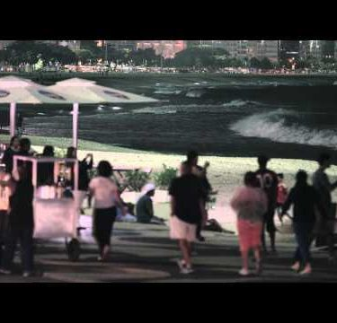 Close up static shot of street vendors and pedestrians on copacobana beach.