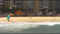 Panning shot of parasailing surfing on Copacabana beach.