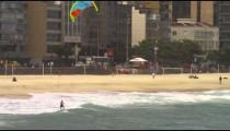 Panning shot of parasailing surfer catching a wave in Rio.