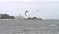 Panning shot from shore of parasailing surfers and cityscape.