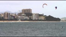 Pan shot of three parasailing surfers with Copacabana city.