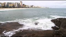 Static shot of rocks and waves with Copacabana city.