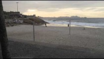 Dog owners play with their dogs in the distance at Ipanema Beach in Rio de Janeiro.
