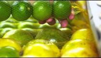 Close-up shot of a person checking out some green mandarin oranges at a market in Rio de Janeiro