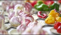 Close-up panning shot of purple garlic and pepper varieties in a market in Rio de Janeiro, Brazil