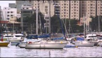 Panning shot of marina with several boats along the coastline in Rio de Janeiro, Brazil