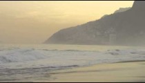 Slow motion pan of surfers and people enjoying Ipanema beach