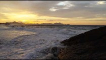 Camera pans from the cliffs to the water at Ipanema Beach in Rio de Janeiro