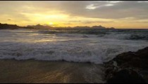 Slow motion, dolly out of the waves rolling up onto Ipanema beach