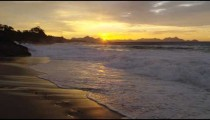 Slow motion, dolly out as the tide rolls in at sunset against the rocks on Ipanema beach
