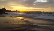 Slow motion, dolly out as waves crash against Ipanema beach at sunset