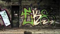 Slow motion dolly shot of graffiti art on walls along a street in Rio de Janeiro, Brazil
