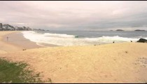 Slow motion pan of man doing headstand on the beach in Rio de Janeiro, Brazil