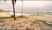 Slow motion tracking shot of man doing headstand on the beach in Rio de Janeiro, Brazil