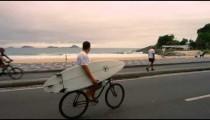 RIO DE JANEIRO-JUNE 23: Man bikes while holding surfboard near Ipanema Beach on Jun 23, 2013 in Rio