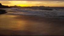 Slow motion, tilt up from ocean ripple to waves on Praia do Diabo (Devil's Beach)