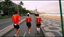 Slow tracking shot of three runners running along the street near Ipanema beach in Rio, Brazil